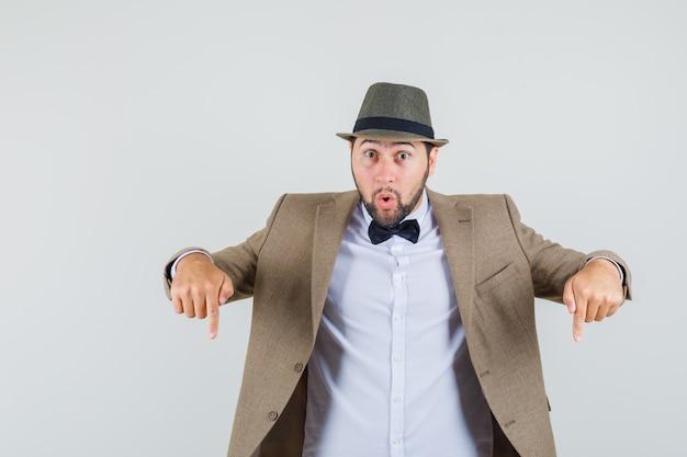 Jovem de terno, chapéu apontando para baixo e olhando surpreso, vista frontal.