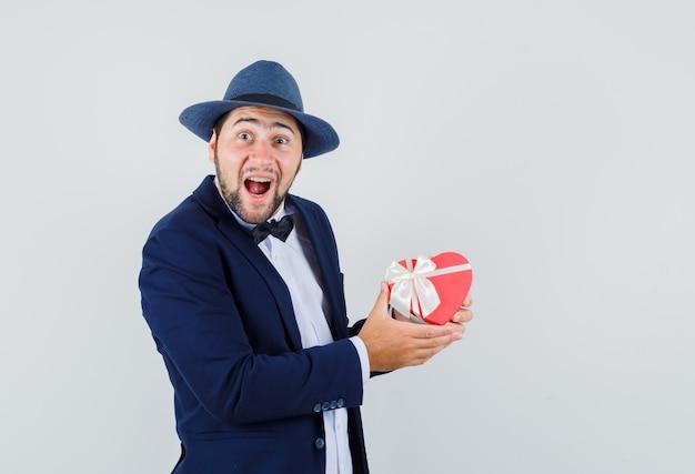 Jovem de terno, chapéu segurando a caixa de presente e olhando feliz, vista frontal.