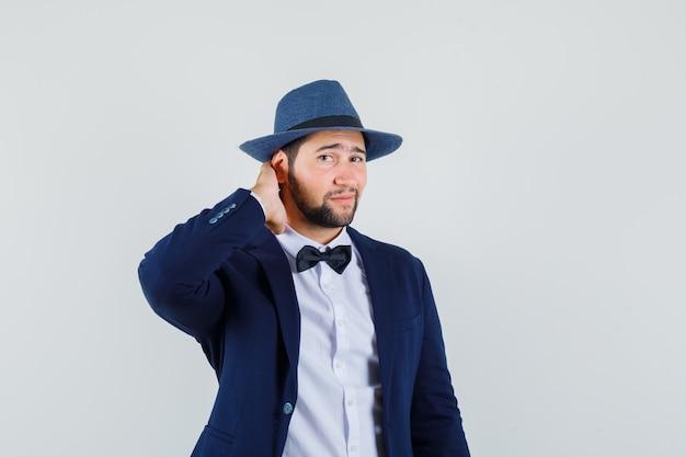 Jovem de terno, chapéu segurando a mão no pescoço e olhando bonito, vista frontal.