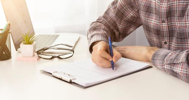 Jovem de terno escrevendo jornais de negócios na mesa no escritório de coworking moderno. copie o espaço
