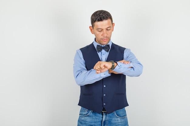 Jovem de terno, jeans olhando para o relógio e parecendo pontual Foto gratuita