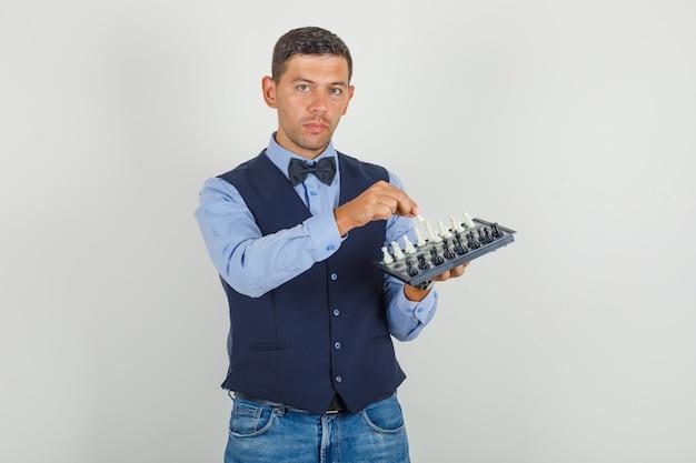 Jovem de terno, jeans segurando o tabuleiro de xadrez e a figura