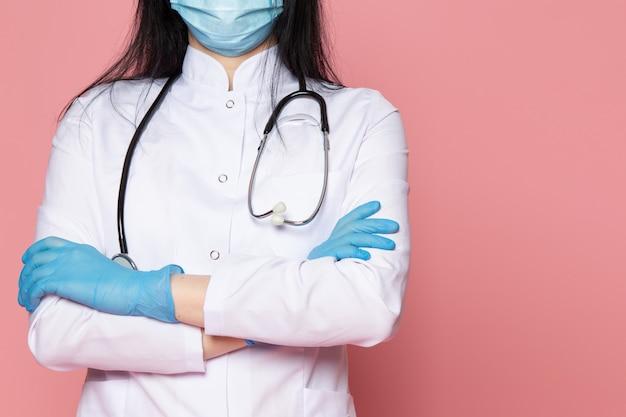 Jovem de terno médico branco azul luvas azul máscara protetora com estetoscópio na rosa