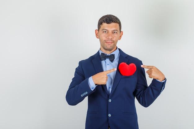 Jovem de terno mostrando um coração vermelho no bolso e parecendo alegre