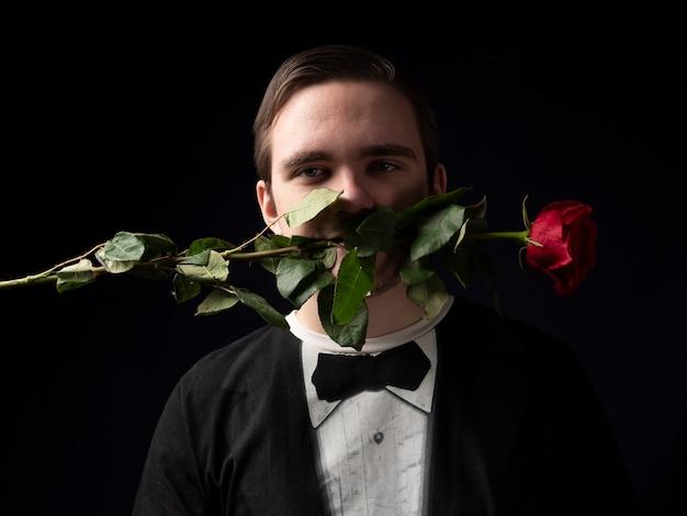 Jovem de terno preto segurando uma rosa vermelha entre os dentes