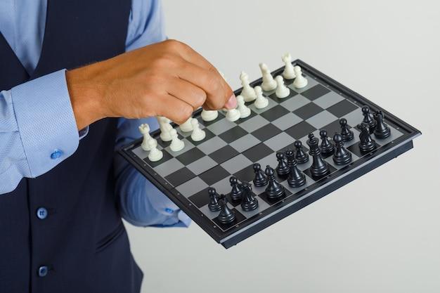 Jovem de terno segurando um tabuleiro de xadrez e uma figura