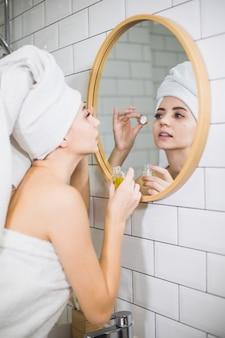Jovem de toalha branca aplica óleo hidratante na pele do rosto. conceito de autocuidado, beleza e cuidados com a pele.