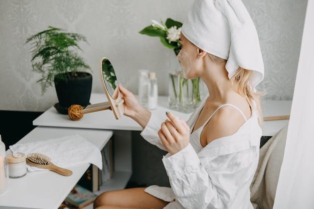 Jovem de toalha branca relaxando no quarto e fazendo máscara facial de argila perto do espelho.