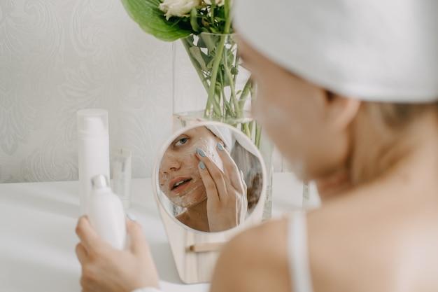 Jovem de toalha relaxando no quarto e fazendo máscara facial de argila perto do espelho. rotina matinal