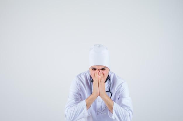 Jovem de uniforme branco, mantendo as mãos em gesto de oração e olhando esperançoso, vista frontal.