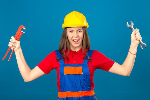 Jovem de uniforme de construção e capacete de segurança amarelo em pé com as mãos levantadas, segurando as chaves ajustáveis, irritadas e frustradas, gritando com raiva no fundo isolado azul
