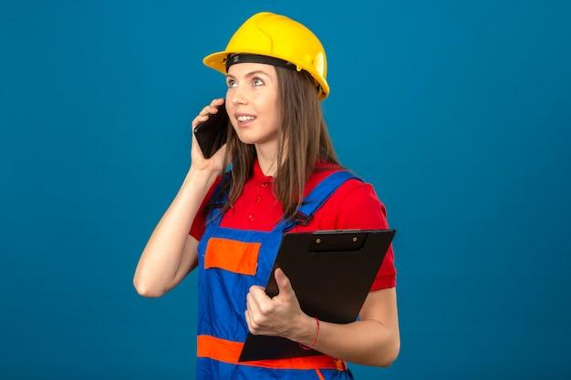Jovem de uniforme de construção e capacete de segurança amarelo segurando a área de transferência e falando pelo smartphone com um sorriso no rosto em pé sobre fundo azul