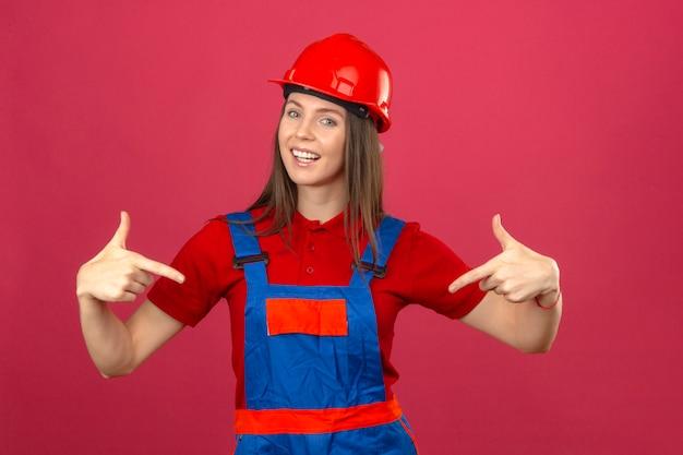 Jovem de uniforme de construção e capacete de segurança vermelho sorrindo e apontando para si mesma parece alegre em pé no fundo rosa escuro