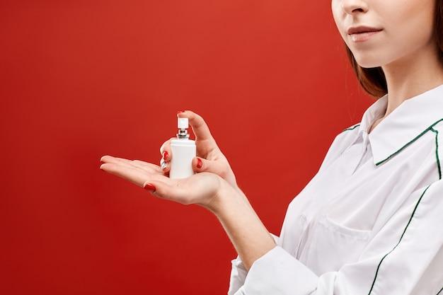 Jovem de uniforme médico, mostrando um frasco de spray com desinfetante no fundo vermelho, médica mantém um spray com medicamento na palma da mão aberta