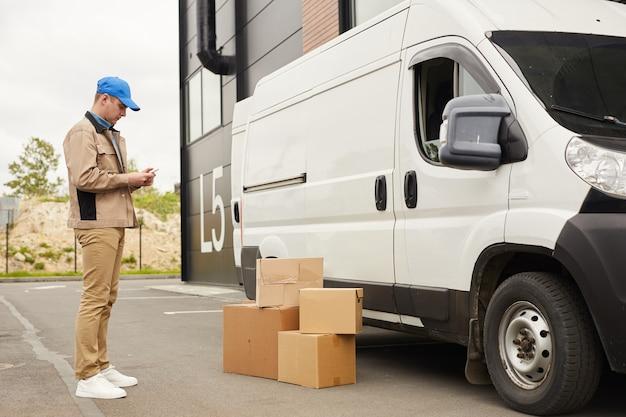 Jovem de uniforme usando seu telefone celular em pé perto da van e pacotes ao ar livre perto do armazém