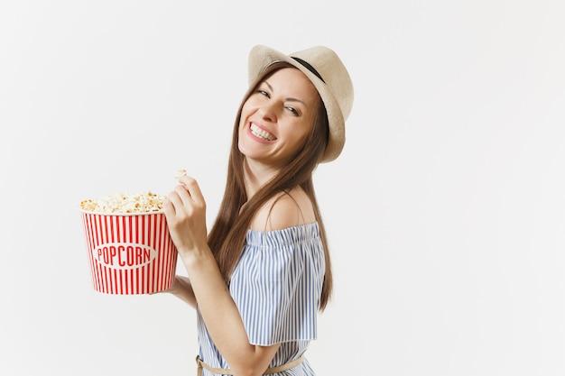 Jovem de vestido azul, chapéu, assistindo filme filme segurando, comendo pipoca de balde, isolado no fundo branco. pessoas, emoções sinceras no cinema, conceito de estilo de vida. área de publicidade. copie o espaço.