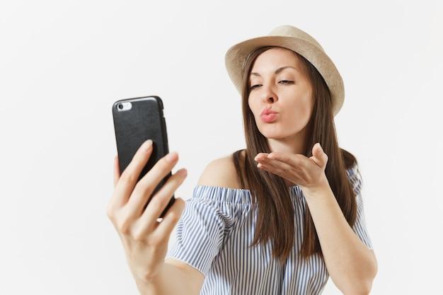 Jovem de vestido azul, chapéu mandando beijos, fazendo selfie filmado no celular ou videochamada isolada no fundo branco. pessoas, emoções sinceras, conceito de estilo de vida. área de publicidade. copie o espaço.
