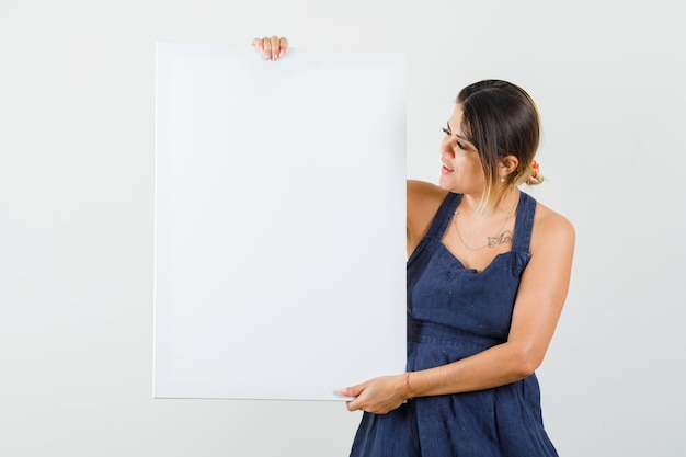 Jovem de vestido segurando uma tela em branco e parecendo focada