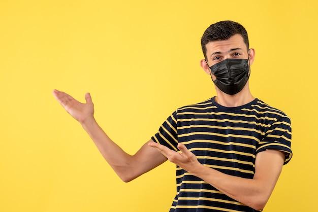 Jovem de vista frontal com camiseta listrada em preto e branco mostrando as costas em fundo amarelo
