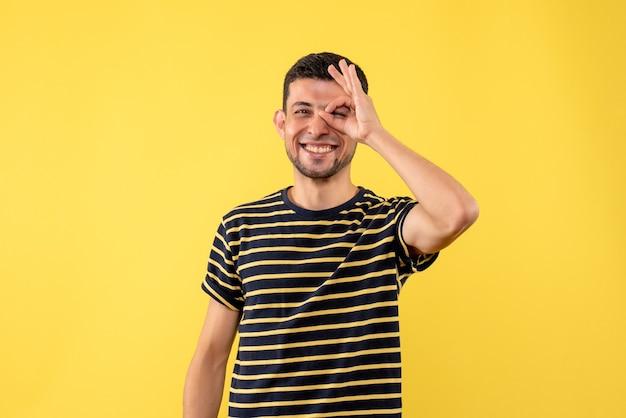 Jovem de vista frontal em uma camiseta listrada em preto e branco, colocando um sinal de ok na frente de seus olhos em um fundo amarelo isolado