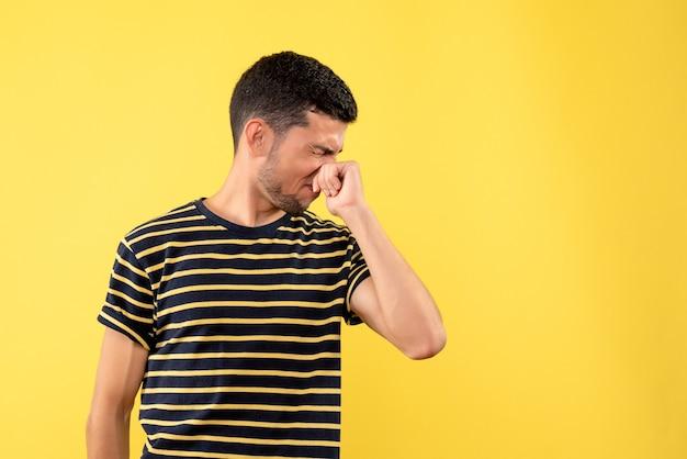 Jovem de vista frontal em uma camiseta listrada preto e branco fechando o nariz em um fundo amarelo isolado