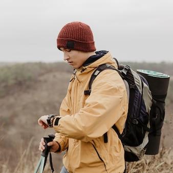Jovem de vista lateral com equipamento de viagem