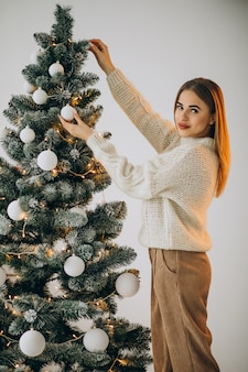 Jovem decorando uma árvore de natal