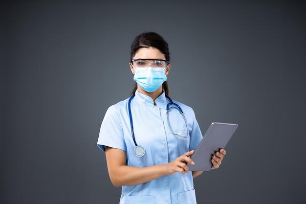 Jovem dedicada e inovadora médica com máscara facial e óculos de proteção usando tablet para fazer agendamento.