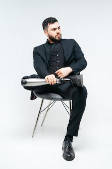 Jovem deficiente com perna protética, sentado em uma cadeira no estúdio sobre parede branca, conceito de membro artificial