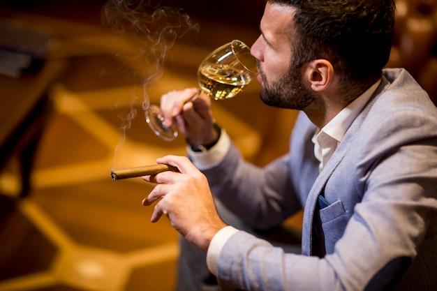 Jovem, degustação de vinho branco e fumar charuto