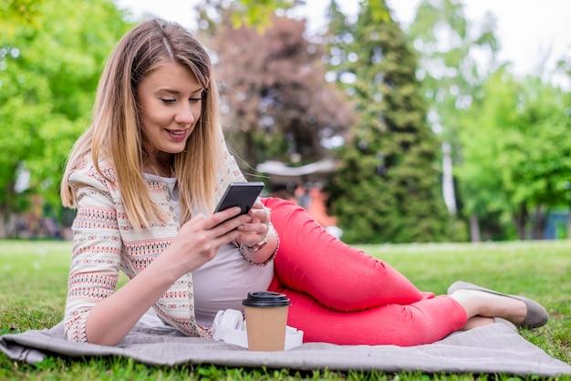 Jovem, deitada na grama da primavera fresca, ouvindo música em seu telefone celular, sorrindo com prazer. jovem feminina que espera que a criança tenha descanso fora no jardim público. mulher grávida que navega internet no telefone celular.