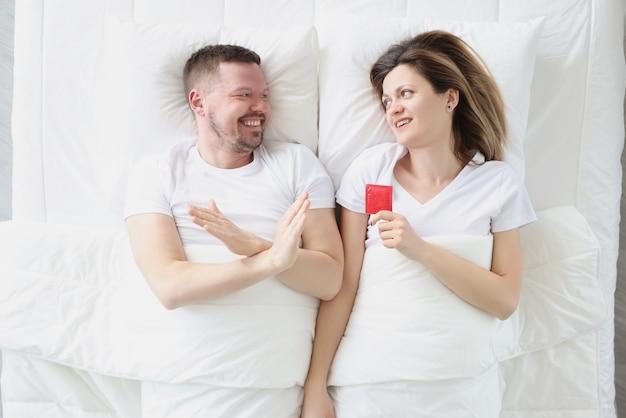 Jovem deitado na cama com uma mulher e recusando a vista superior do preservativo, problemas com a potência nos homens