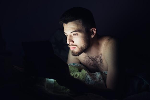Jovem deitado na cama e olhar para a tela do tablet. calma pacífica cara concentrada jogando ou se divertindo. escuro à noite.