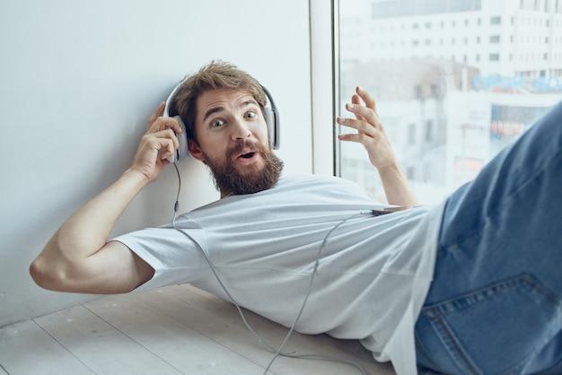 Jovem deitado no parapeito da janela usando tecnologia de fones de ouvido