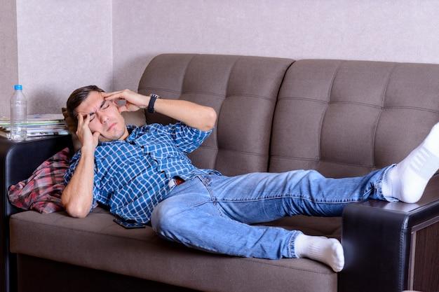 Jovem, deitado no sofá, segurando sua cabeça, dores de cabeça.