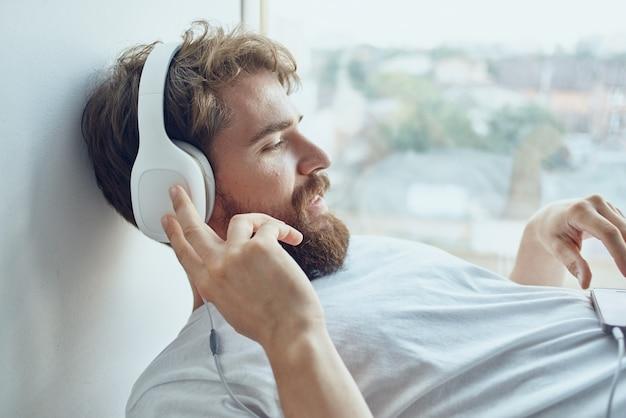Jovem deitado perto da janela usando fones de ouvido hipster