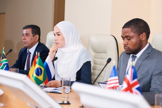 Jovem delegada pensativa em hijab ouvindo um dos colegas relatar enquanto está sentada à mesa entre dois homens interculturais