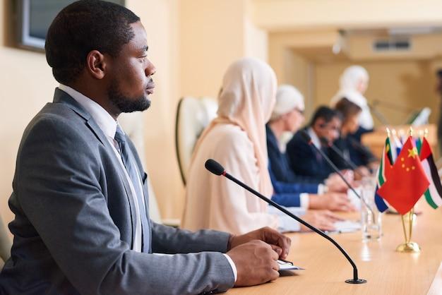 Jovem delegado afro-americano sério e participante de fórum político ouvindo relato de colega estrangeiro
