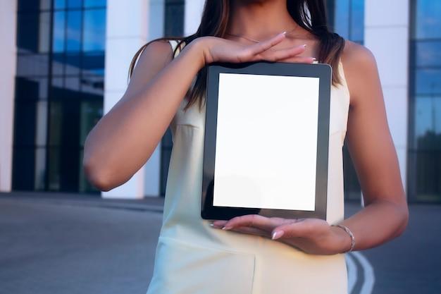 Jovem demonstra a tela do tablet com tela branca