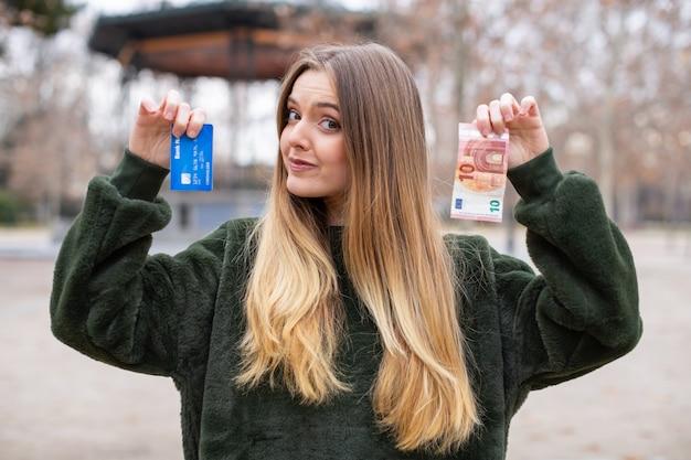 Jovem, demonstrando o cartão de plástico e dinheiro para a câmera em pé no parque