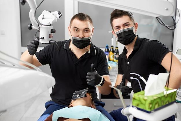Jovem dentista e seu assistente estão olhando para a câmera, mostrando um gesto do dedo com uma classe.