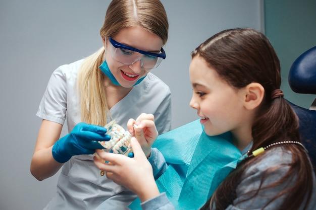Jovem dentista feminina mostrando mandíbula artificial com dentes para menina