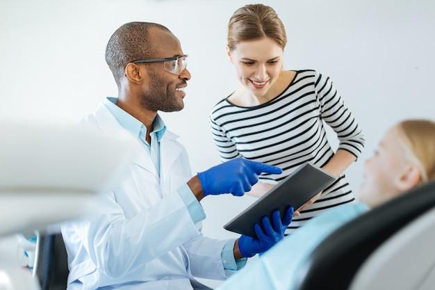 Jovem dentista simpático mostrando uma agenda de consultas no tablet para a mãe de sua pequena paciente enquanto ela escolhe a data da próxima consulta