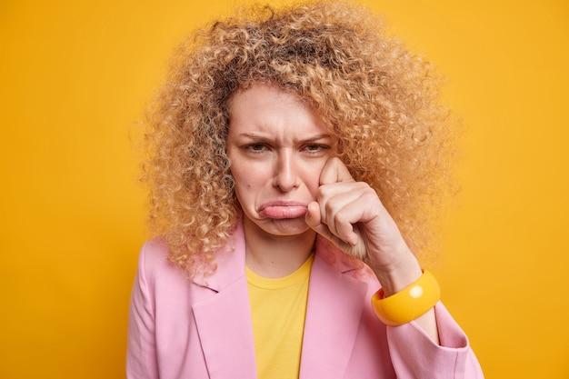 Jovem deprimida de cabelos cacheados enxuga as lágrimas sente muito chateada chora de desespero tem expressão facial abatida preocupada com problemas no trabalho vestida formalmente isolada sobre parede amarela