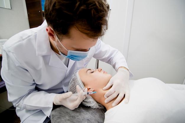 Jovem dermatologista está aplicando injeções para resolver alguns problemas de pele relacionados ao envelhecimento e torná-la macia e saudável.