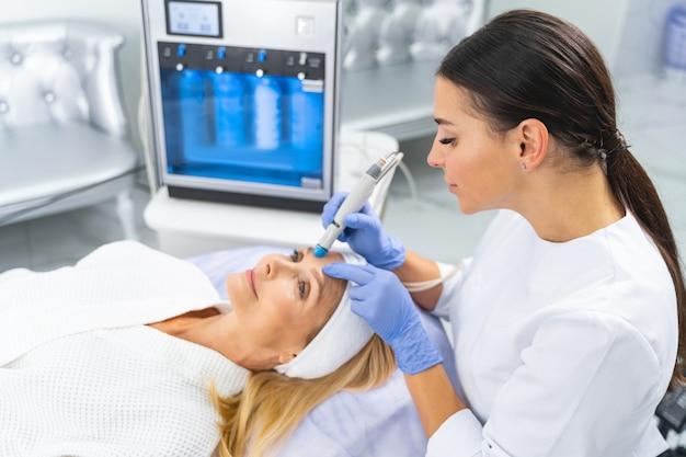 Jovem dermatologista profissional de cabelos escuros, caucasiana, realizando um procedimento cosmético para melhorar a elasticidade da pele de seus clientes