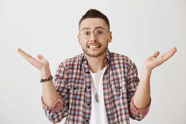 Jovem desajeitado sem noção com óculos posando