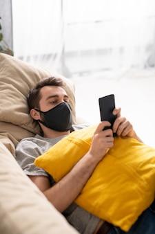 Jovem desanimado com uma máscara preta deitado no sofá na sala de estar e verificando as estatísticas de coronavírus no telefone