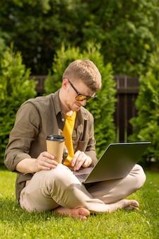 Jovem descalço de óculos amarelos, sentado na grama com o laptop e uma xícara de café descartável. jovem estudante milenar do sexo masculino pesquisando informações para trabalhos de casa usando conexão wi-fi ao ar livre
