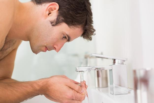 Jovem descamisado lavando rosto no banheiro